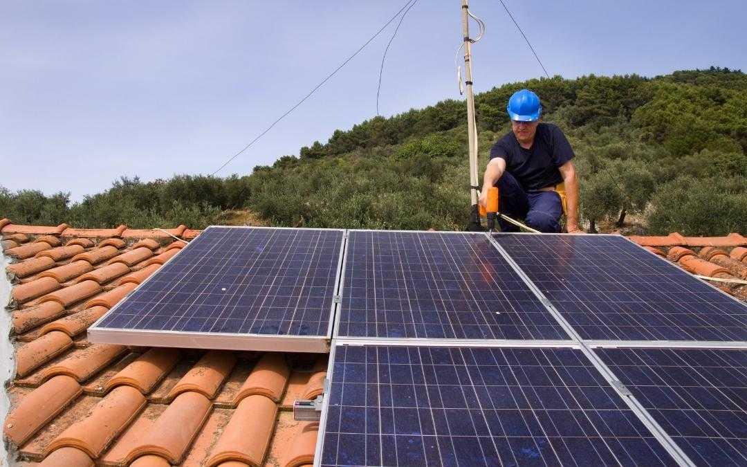 Mężczyzna montuje panele słoneczne na dachu domu jednorodzinnego